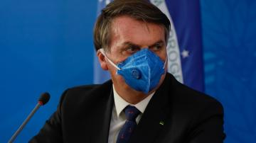 Jair Bolsonaro participa de entrevista à imprensa usando uma máscara de proteção