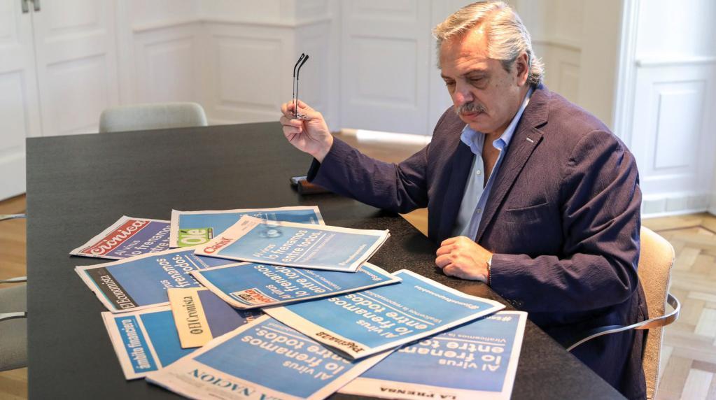 O presidente argentino, Alberto Fernández, observa peça publicitária do governo na capa dos principais jornais do país