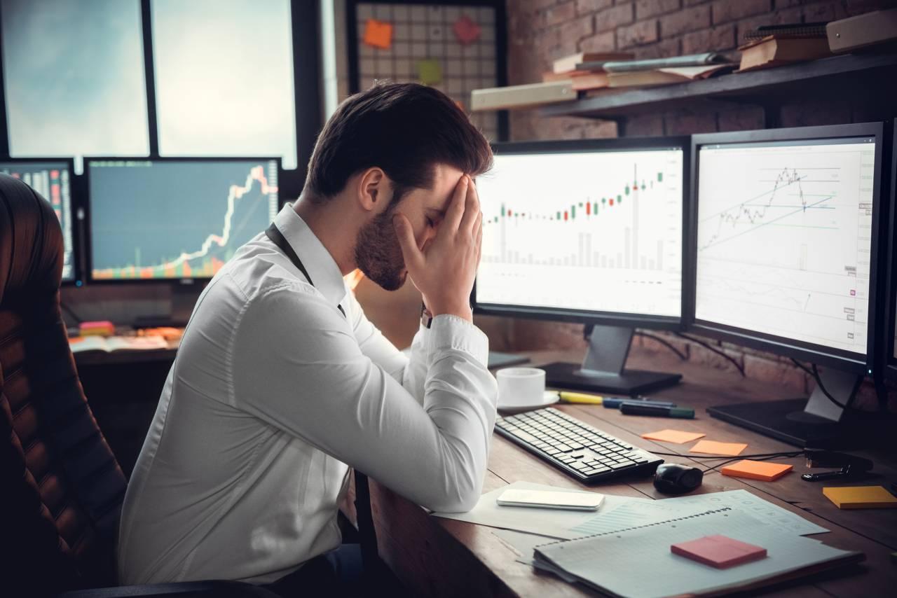 Homem segura o rosto com as mãos, cabisbaixo, diante do computador com gráficos de ações