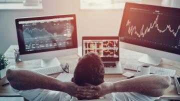 Investidor descansa em frente a telas com cotações de ações