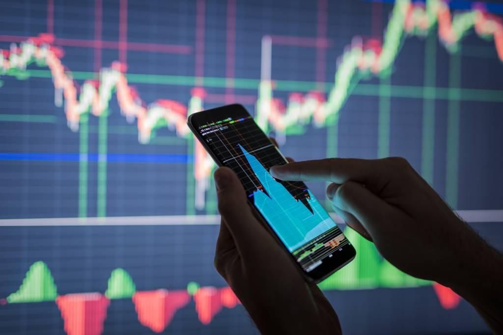 Mão segura um celular e consulta um gráfico em frente a um painel de movimentação de ações em Bolsa - mercado fracionário