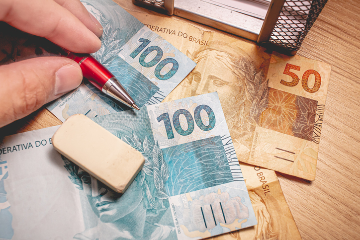 Real - Brazilian Currency. Money bills on a wooden table and a man holding a pen.