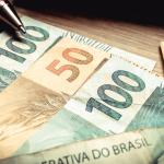 Brazilian currency. Money on the wooden table in one hundred and fifty reais banknotes.