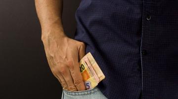 Homem com notas de dinheiro em reais no bolso