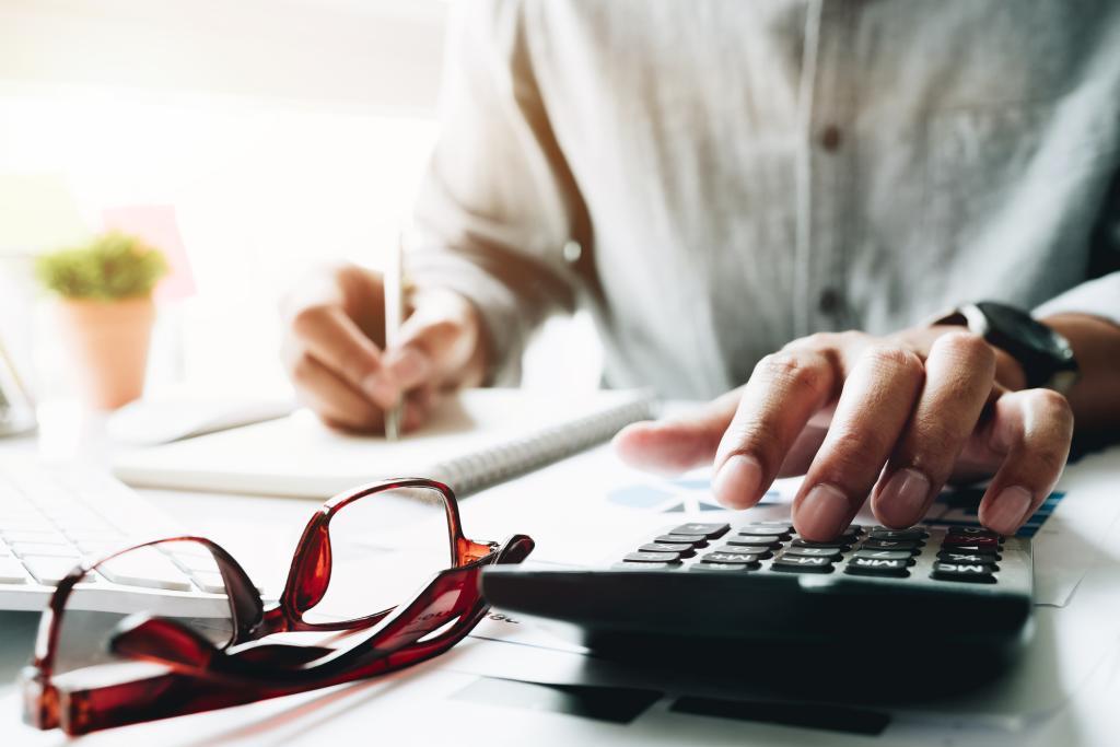 Homem usando calculadora e anotando