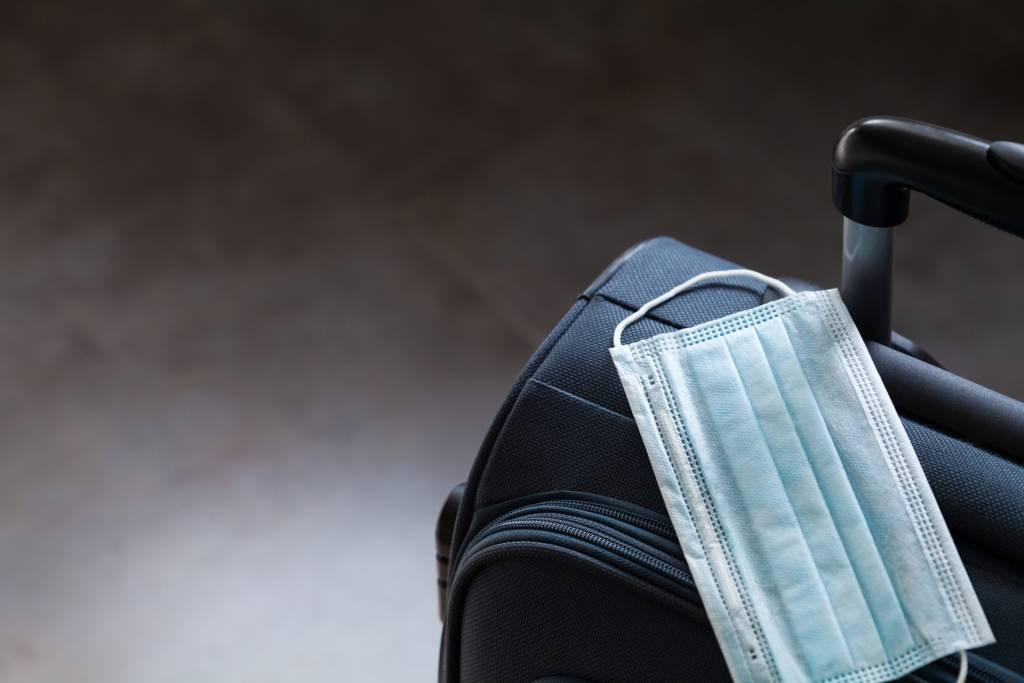Mala de viagem com máscara, representando turismo em tempos de pandemia