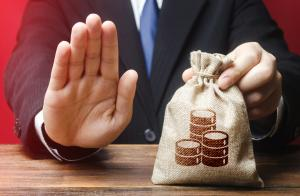 Crédito negado, homem faz sinal de negativo com uma mão enquanto segura saco de dinheiro com a outra, problemas financeiros, falta de dinheiro