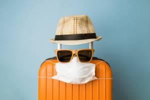 Turismo na pandemia, mala de viagem com máscara