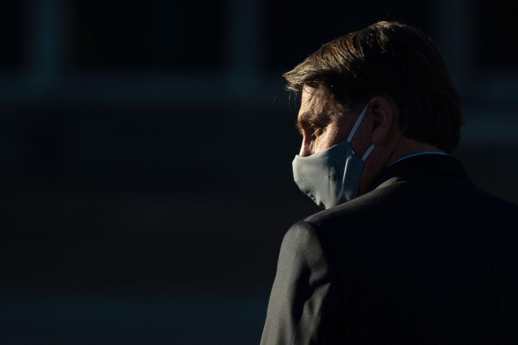 Foto de Bolsonaro usando uma máscara cirúrgica no rosto enquanto caminha em Brasília