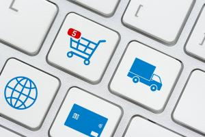 Online shopping / ecommerce and retail sale concept : Shopping cart, delivery van, credit card, world globe logo on a laptop keyboard, depicts customers order things from retailer sites using internet