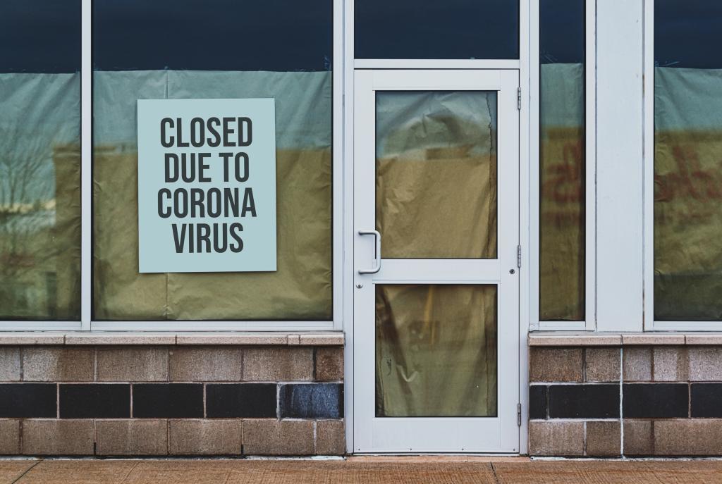 Fachada de loja com placa de fechado devido ao coronavírus pendurada