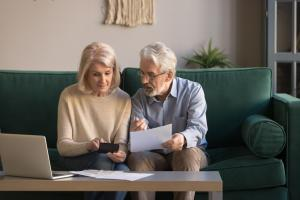 Serious mature couple calculating bills, checking domestic finances