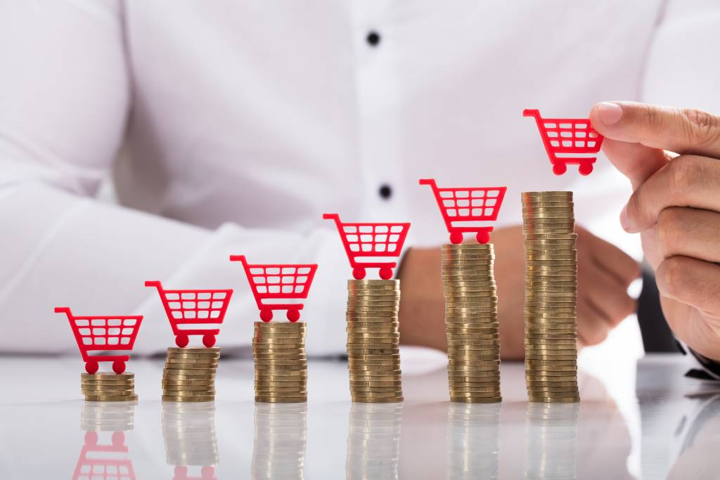 Businessperson placing shopping cart over stacked coins
