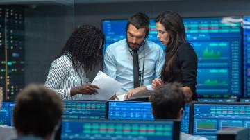 Time de analistas junto a gráficos, profissionais do mercado financeiro, brokers