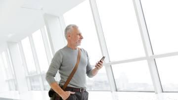 Homem grisalho mexendo no celular, homem mais velho