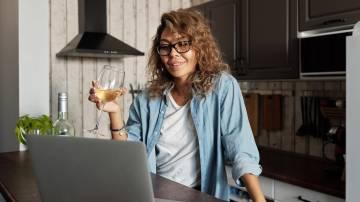 Mulher bebendo vinho e usando o computador (Matilda Wormwood/Pexels)