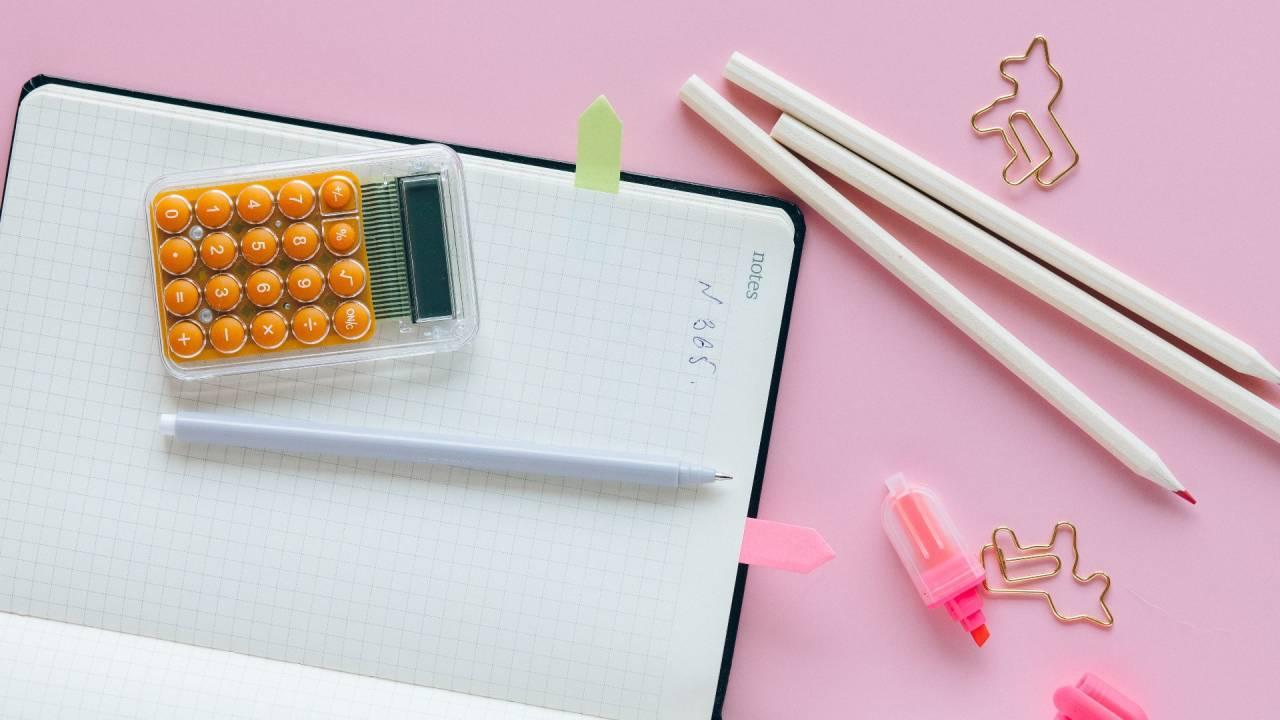 Caderno, calculadora e clipes de unicórnios